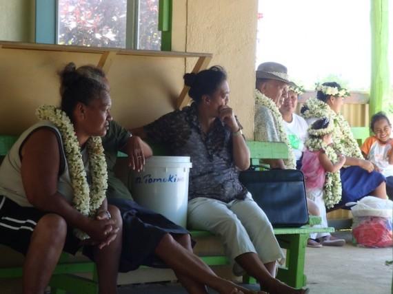 Locals waiting at Atiu airport, adorned with Ei Kaki (flower garlands).