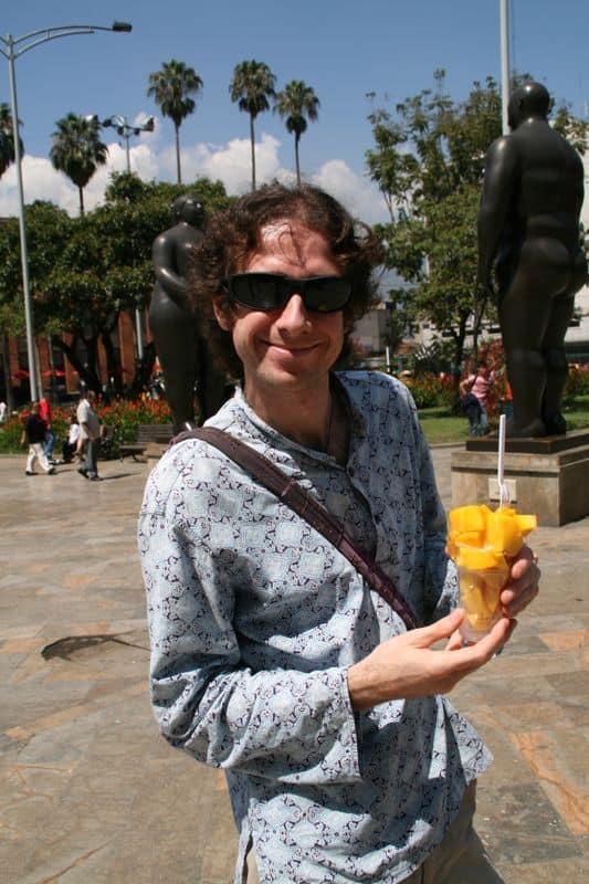 Simon eating mango in Plaza Botero, Medellin
