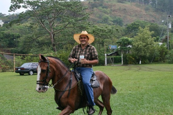 Costa Rican cowboy drinking on horse back
