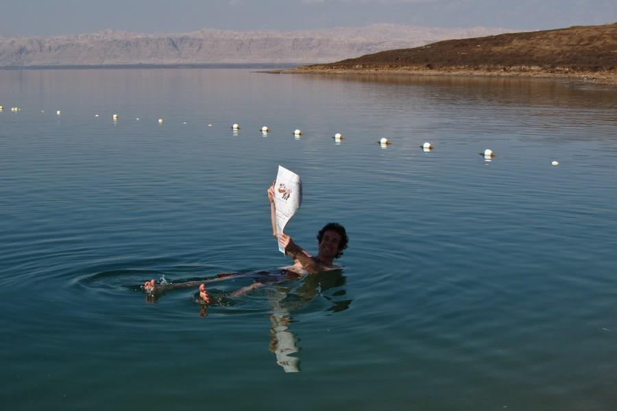 Simon reading a newspaper in the Dead Sea, Jordan
