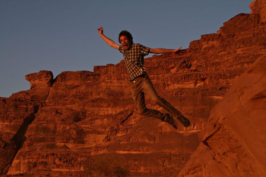 Simon jumping off the rocks at Wadi Rum