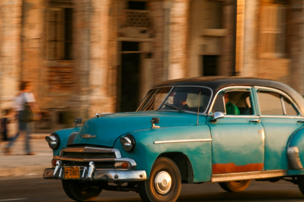 A turquoise car races along the Malecón with the sun turning the old building behind it orange
