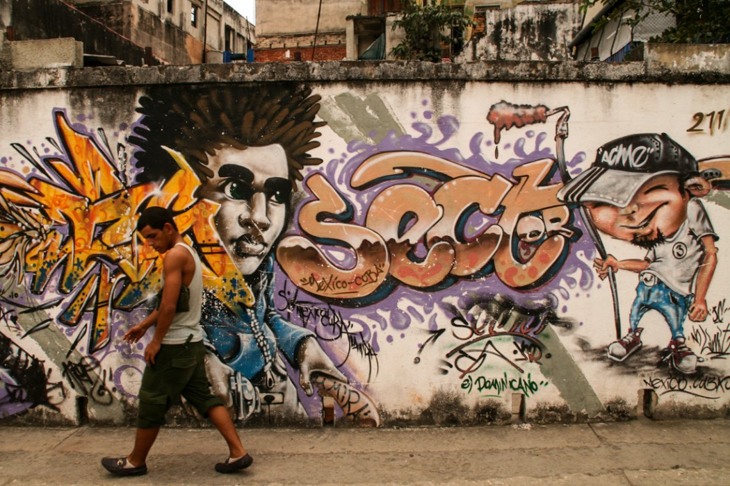 A man walks past a wall painted with Cuban graffiti which features a picture of a man's head and the word 'sect'