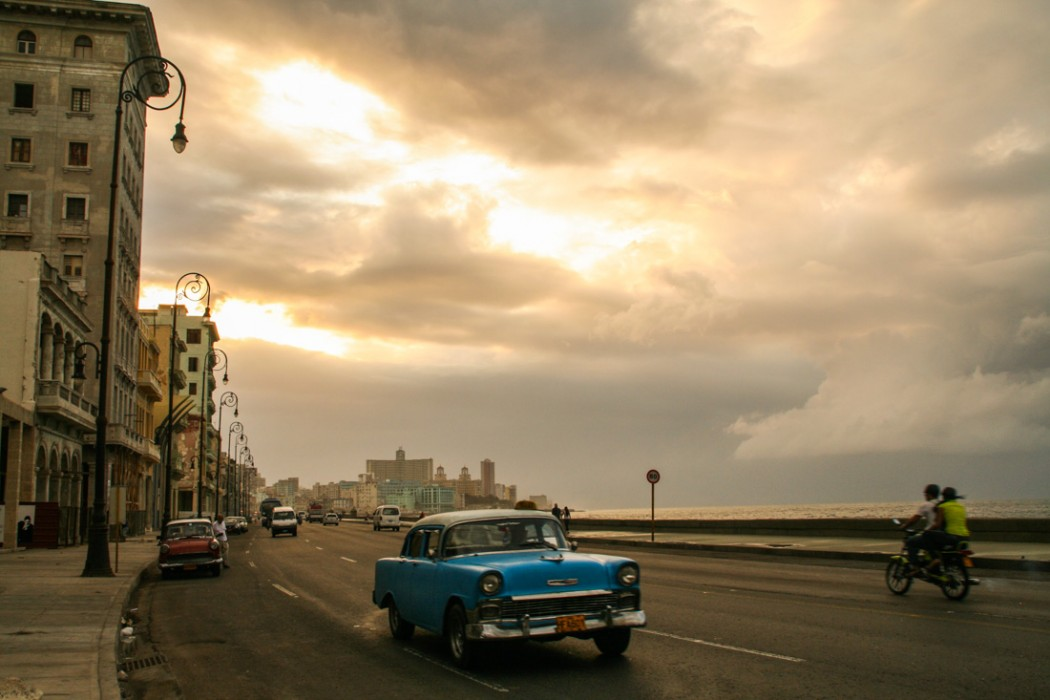 A blue chevrolet with the eagle ornament flies down the Malecón as the sun lights up the clouds behind