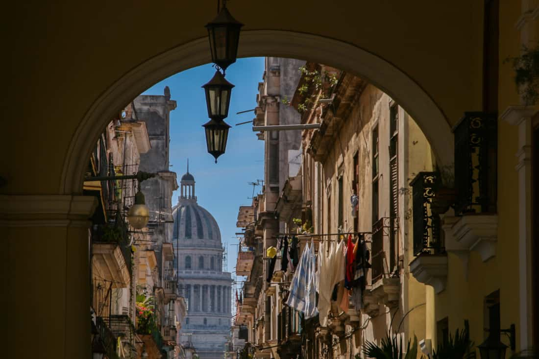 An arch frames a house with its washing hung out as the Cuban capital building stands in the background