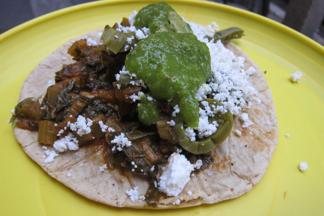 Chard taco topped with cactus, cheese, and green salsa