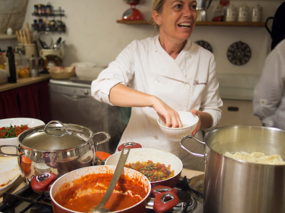Gianna adding capers to the peperonata