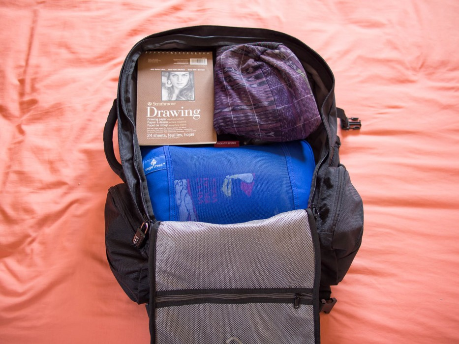 Simon's backpack packed. Packing cube at the bottom with toiletry and accessory cases on top with the iPad, sketch pad and bag above them. His laptop is stored in the laptop compartment behind. Small items in the side pockets.