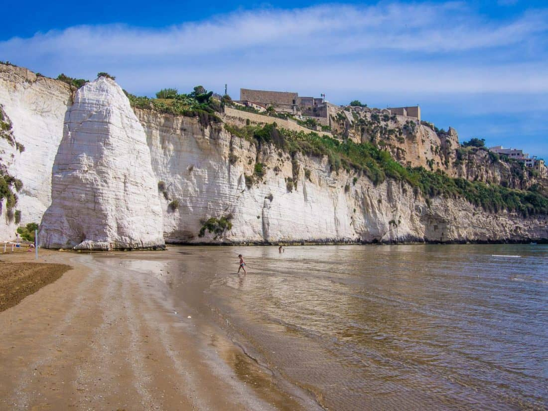Pizzomunno rock at the end of Castello beach and the castle just above it in Vieste Puglia in southern Italy
