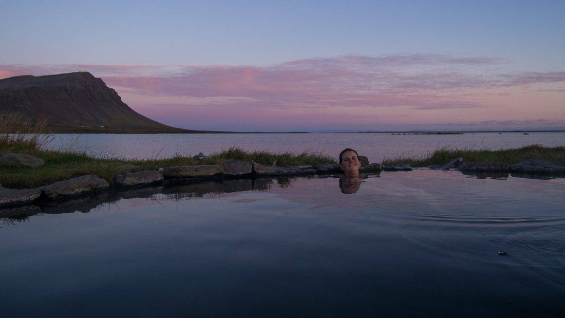 Enjoying an Icelandic hot pot at sunset at Birkimelur Swimming Pool in the Westfjords.
