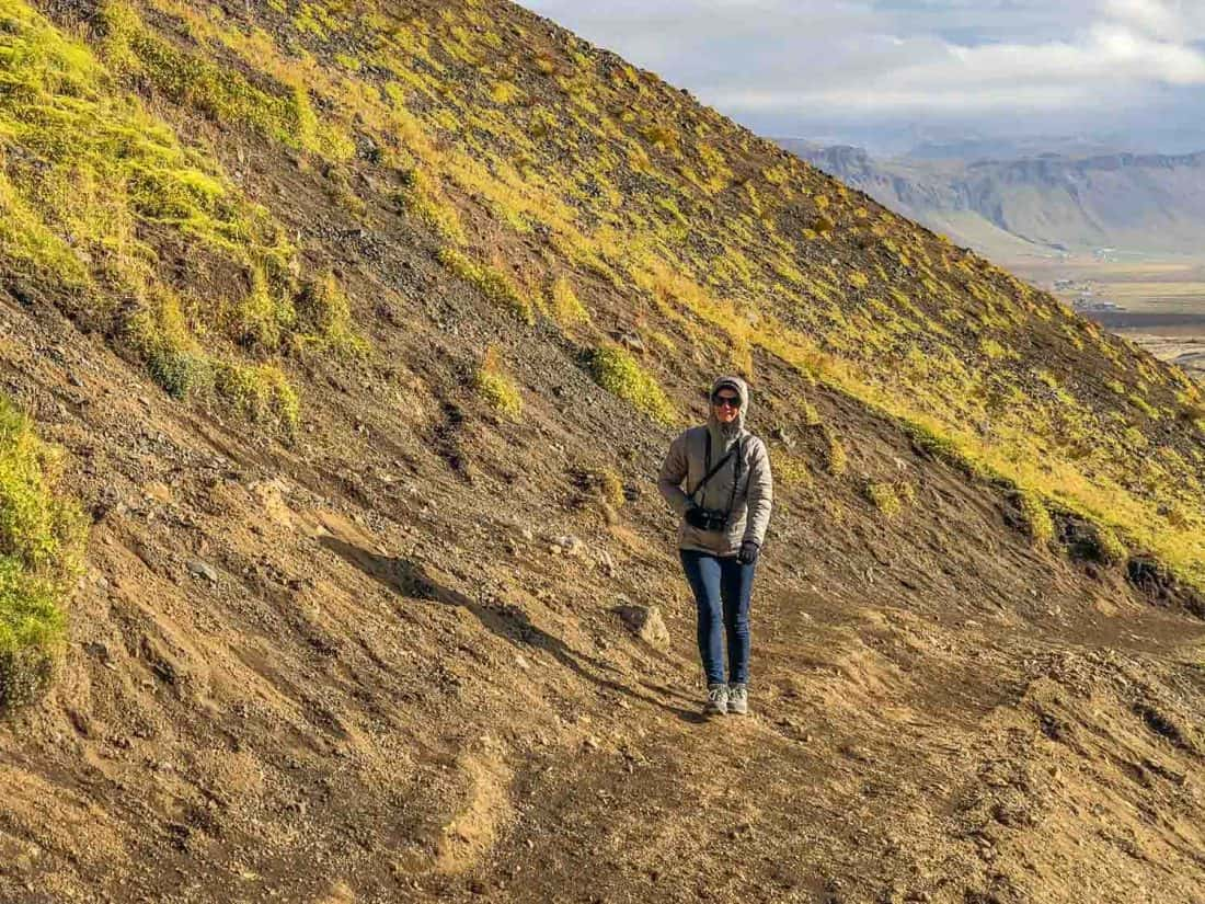 What to wear in Iceland - Erin walking up to Rauðfeldsgjá Gorge in down jacket, jeans and hiking shoes
