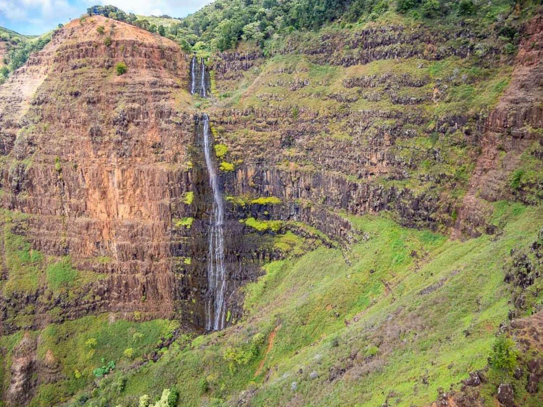Waterfall at Waimea Canyon on a doors off helicopter Kauai tour with Jack Harter in Hawaii