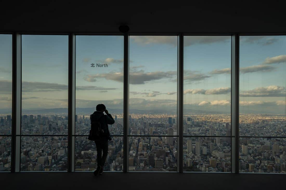 Person taking photos of view of north Osaka at Harukas 300 just before sunset