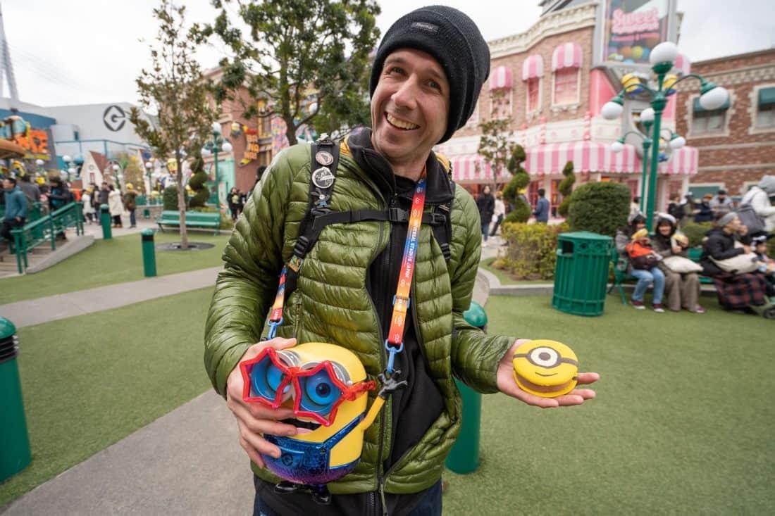 Simon Fairbairn with a Minion popcorn bucket and cookie sandwich in Minion Park at Universal Studios Osaka