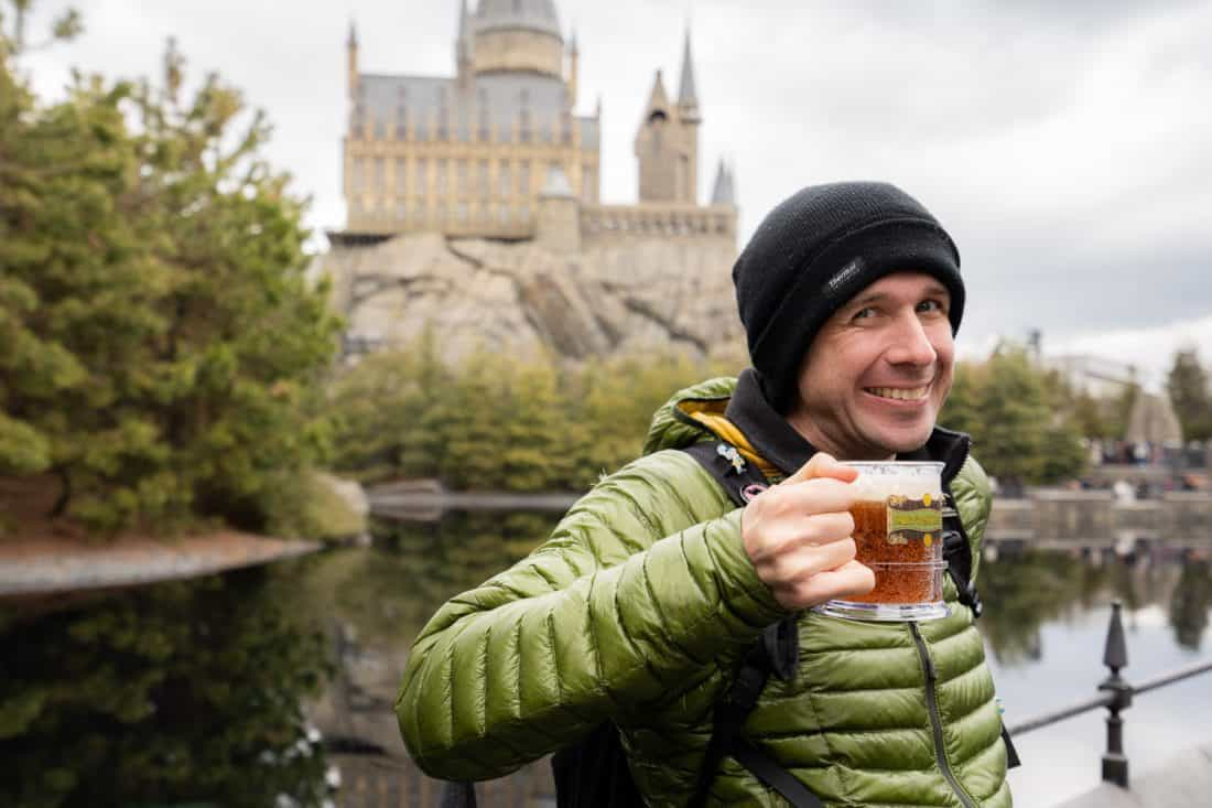 Simon drinking butterbeer on the terrace of the Three Broomsticks with Hogwarts Castle behind him at The Wizarding World of Harry Potter at Universal Studios Japan in Osaka