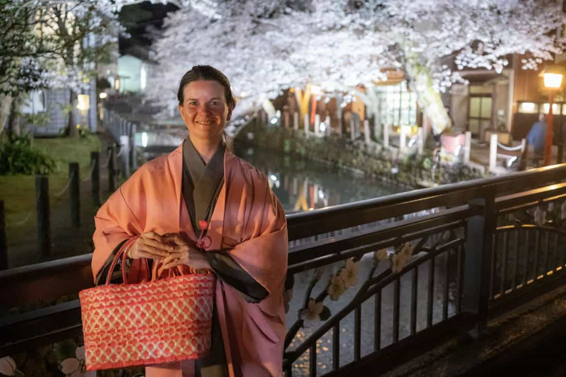 Erin in kimono by the cherry blossom lined canal in Kinosaki Onsen