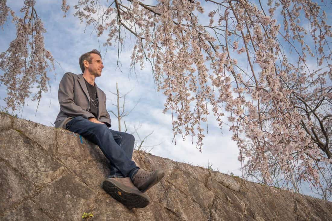 Bluffworks jeans review - Simon wearing the Departure travel jeans under the cherry blossoms in Kyoto