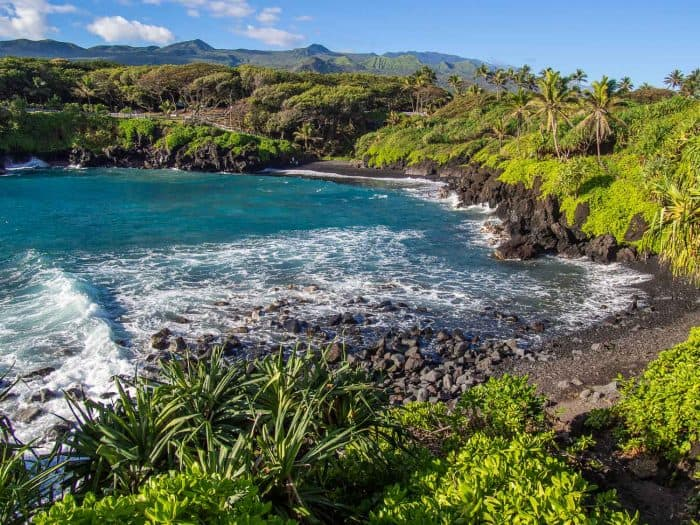 The black sand beach at Waianapanapa State Park, one of the best road to Hana stops on the island of Maui in Hawaii