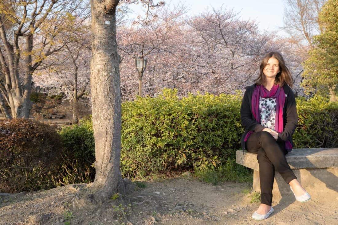 Erin wearing vegan Tieks in the cherry blossom gardens at Himeji Castle in Japan