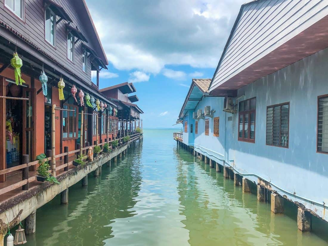 Blue and brown wooden houses on stilts over the water in Old Town on the East Coast of Koh Lanta, Thailand