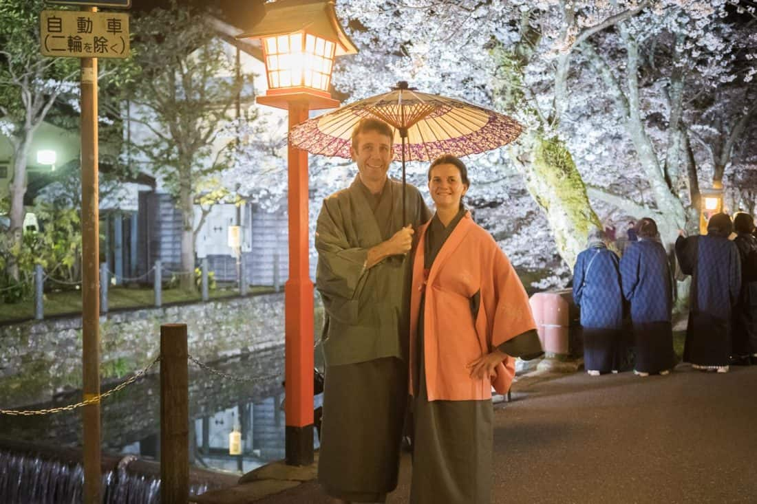 Erin and Simon in winter kimonos by the cherry blossom lined canal at night at Kinosaki Onsen Town, one of the best things to do in Japan