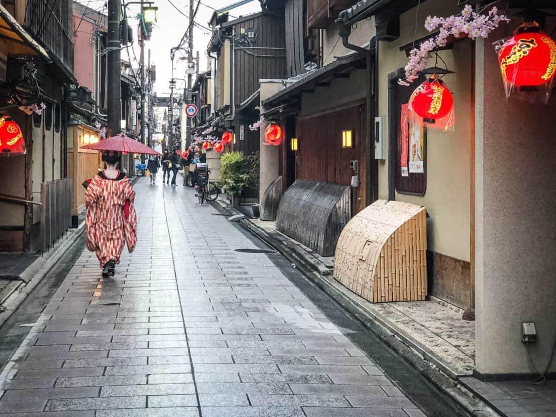 A maiko (apprentice geisha) in the rain on a street in Miyagawacho near Gion, Kyoto