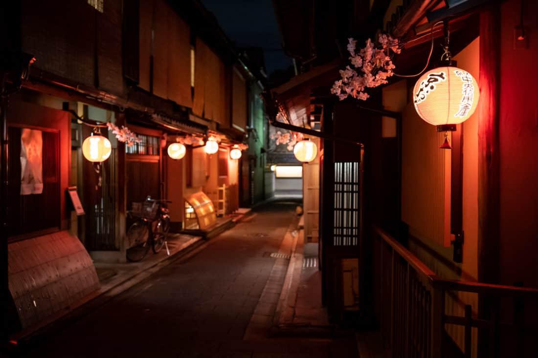 The narrow streets of Miyagawacho near Gion lit up with lanterns at night in Kyoto, Japan