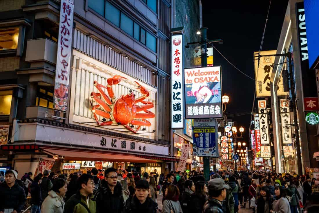 Busy streets and giant crab of Dotonburi in Osaka at night, a popular day trip from Kyoto