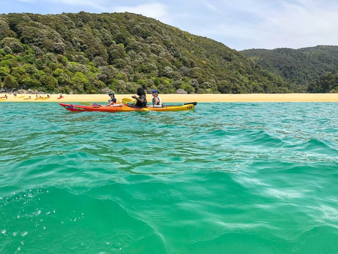 Kayaking past Sandfly Bay in Abel Tasman National Park