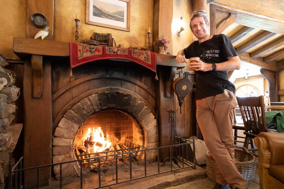Simon enjoying a drink next to the fireplace at the Green Dragon Inn in Hobbiton, New Zealand