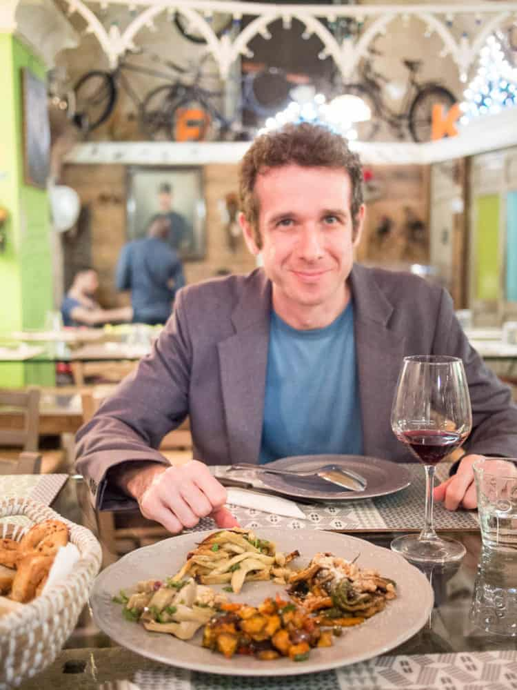 Simon with glass of red wine and vegetarian antipasto in a restaurant in Lecce, Italy