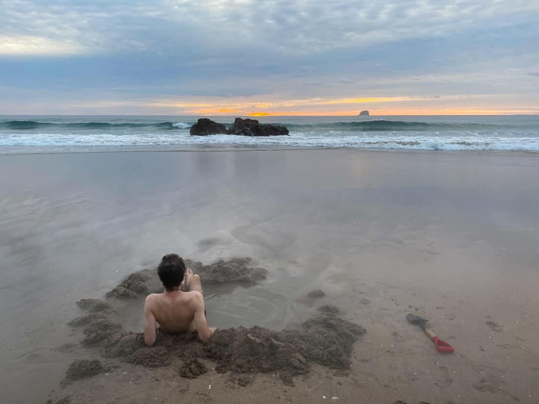 Digging your own spa bath at Hot Water Beach at sunrise on New Zealand's North Island