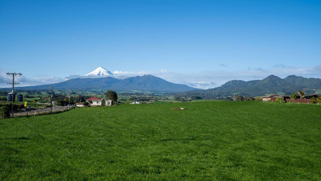 View of snow-capped Mount Taranaki and green farmland while driving around Taranaki region