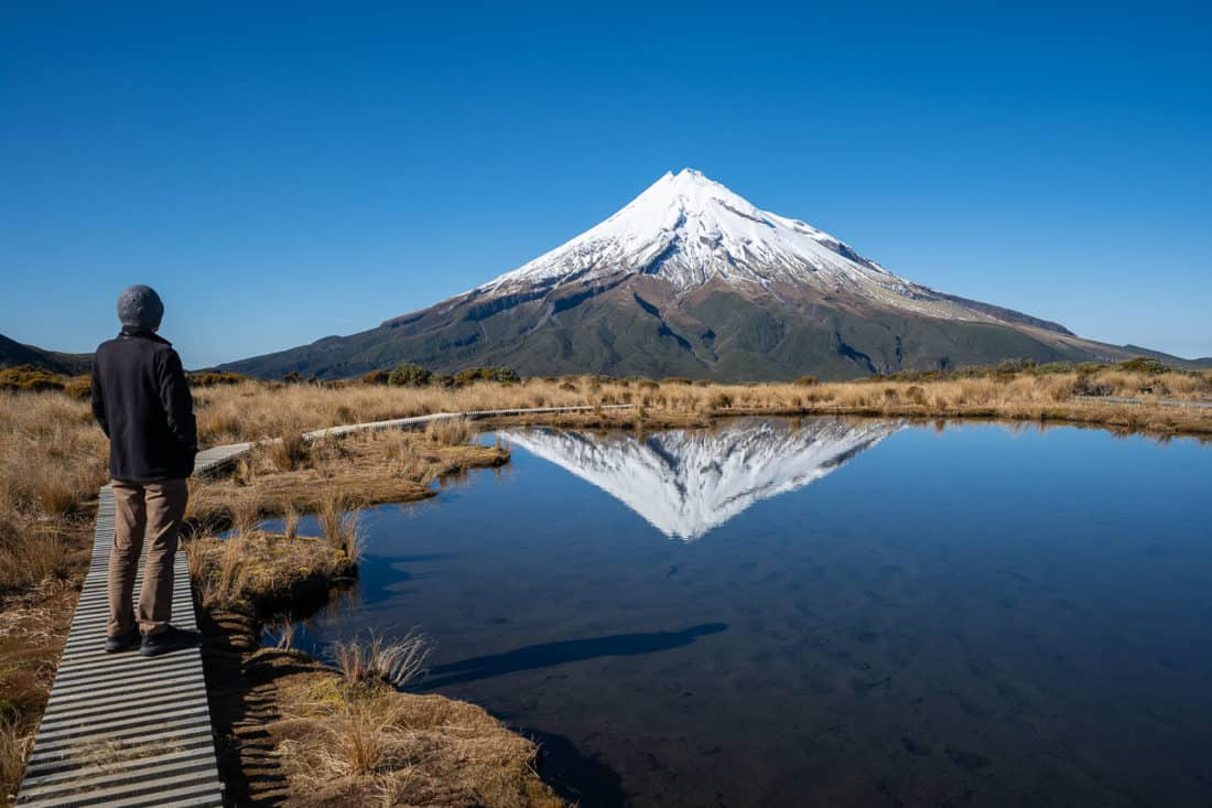 Walking on the boardwalk at Pouakai Tarn with Mt Taranaki reflected in the water on a clear day