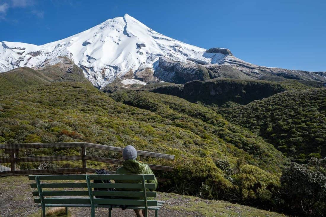 Sitting on a bench at Stratford Plateau with a view of snow-capped Mt Taranaki
