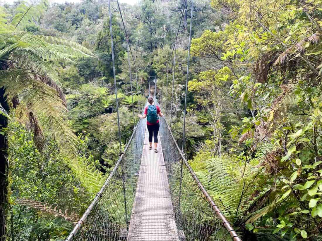 Hiker crossing the Falls River swing bridge on the Abel Tasman coastal track