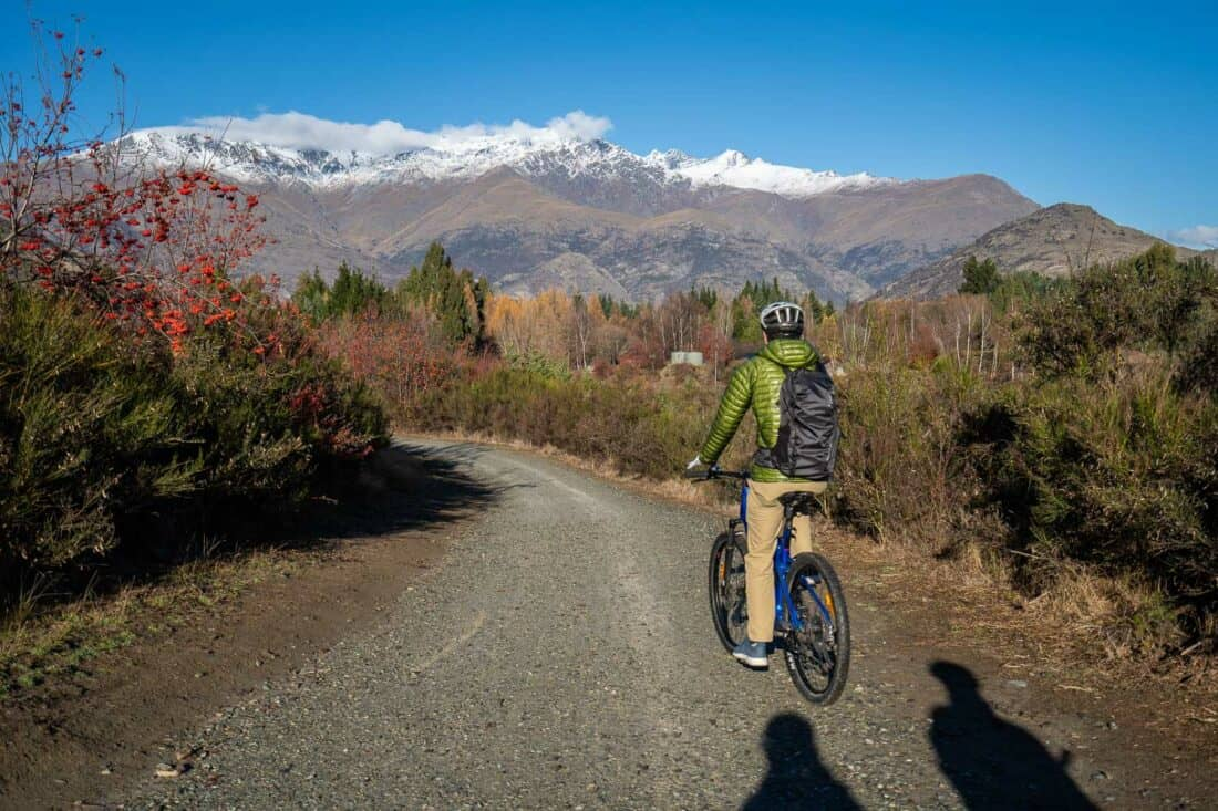 Cycling towards snowy mountains on the Arrowtown to Gibbston Valley bike trail